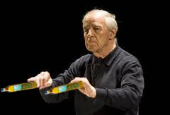 Boulez, conducting, holding olive oil bottles